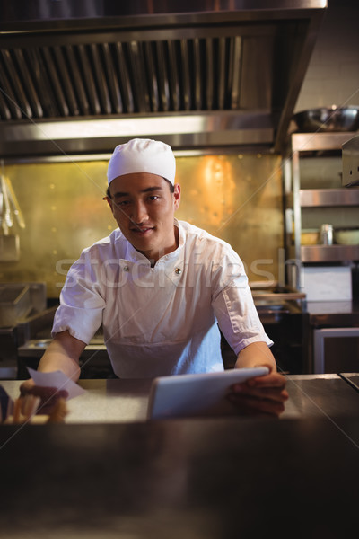 Stock photo: Chef holding digital tablet and an order list in the commercial kitchen
