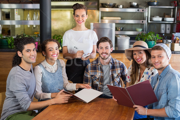 Smiling waitress and customers in restaurant Stock photo © wavebreak_media
