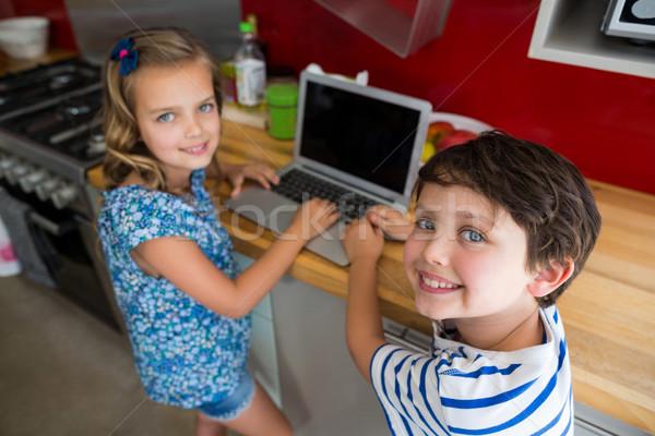 Sonriendo hermanos usando la computadora portátil cocina retrato casa Foto stock © wavebreak_media