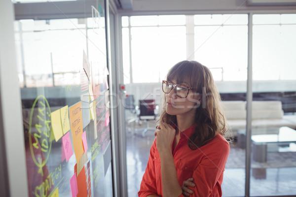 Ernstig zakenvrouw naar zelfklevend merkt kantoor Stockfoto © wavebreak_media