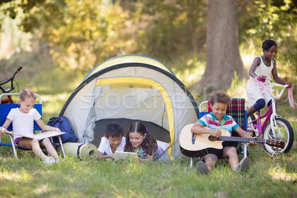 Gyerekek élvezi táborhely nyár nyaralások fű Stock fotó © wavebreak_media