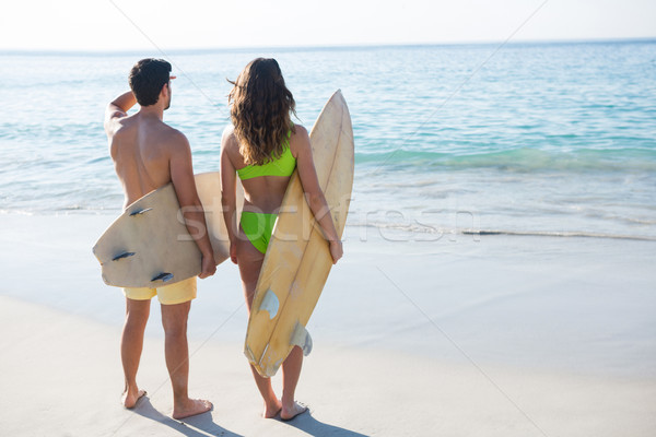 Rear view of couple holding surfboards at beach Stock photo © wavebreak_media