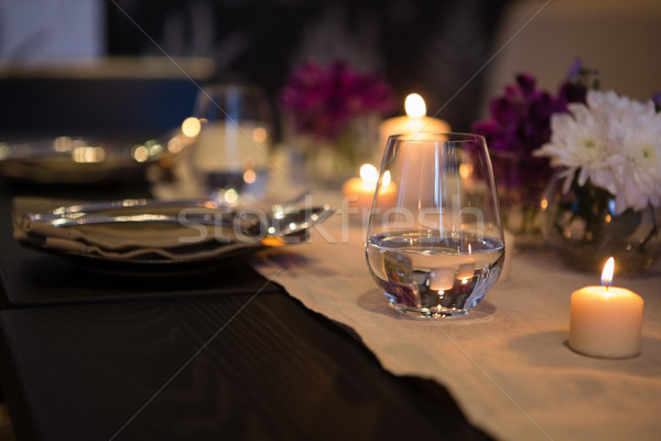 Close up of drinking glass by lit candles on dining table Stock photo © wavebreak_media