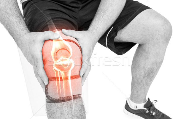Man suffering with knee pain against white background Stock photo © wavebreak_media