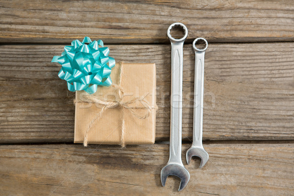 Overhead view of gift by wrenches on table Stock photo © wavebreak_media