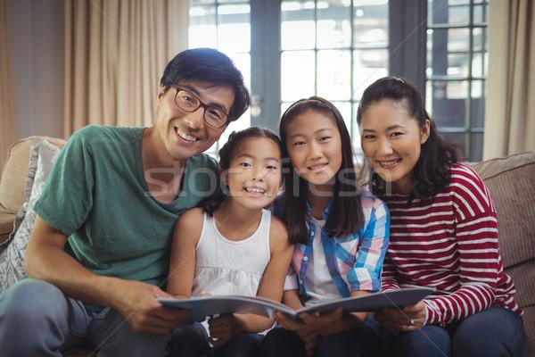Family with photo album together in living room Stock photo © wavebreak_media