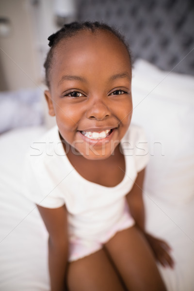 Portrait of smiling girl sitting on bed Stock photo © wavebreak_media