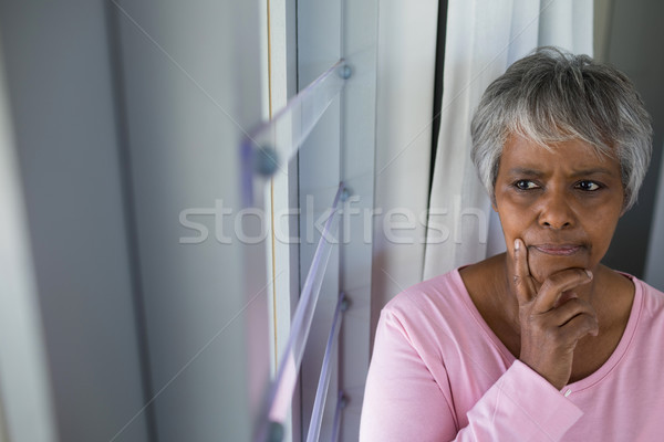 Thoughtful senior woman looking through window in bed room Stock photo © wavebreak_media