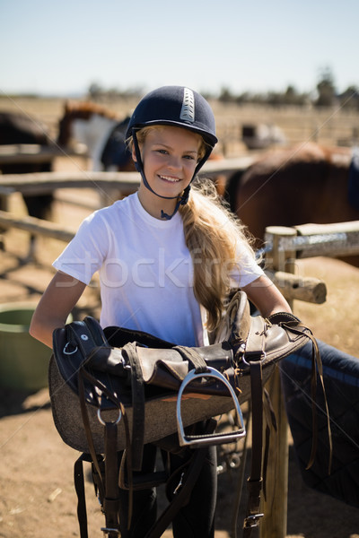 Smiling girl holding horse saddle Stock photo © wavebreak_media