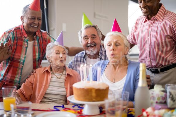 Friends looking at senior woman blowing birthday candles Stock photo © wavebreak_media