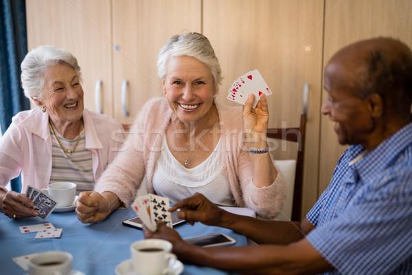 Happy senior people playing cards while having coffee Stock photo © wavebreak_media