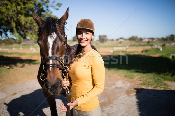 Confident female jockey with horse standing on field Stock photo © wavebreak_media