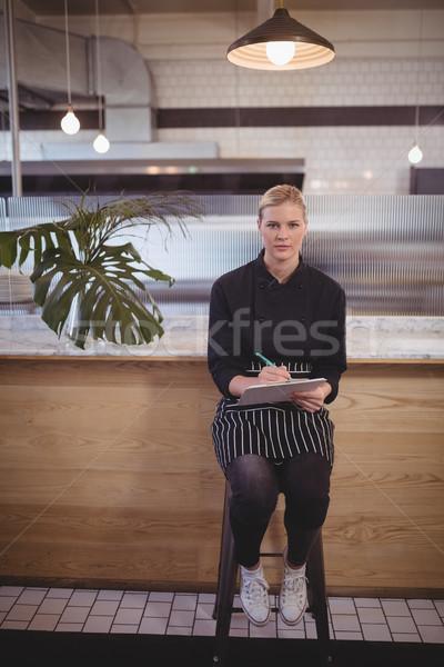 Giovani cameriera seduta appunti coffee shop counter Foto d'archivio © wavebreak_media
