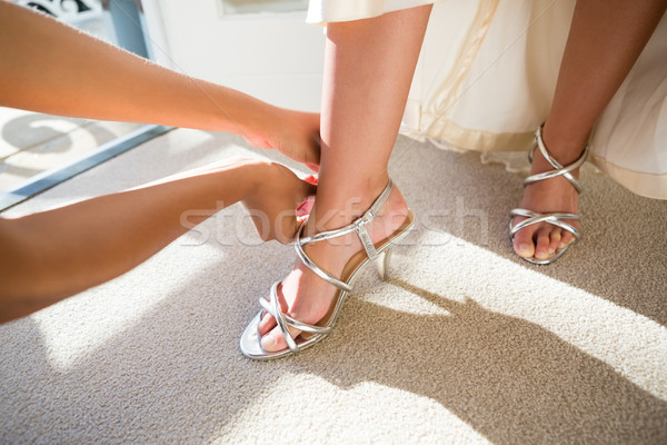 Cropped hands of beautician putting on sandals to bride Stock photo © wavebreak_media