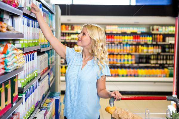 Mujer sonriente toma alimentos plataforma carrito supermercado Foto stock © wavebreak_media
