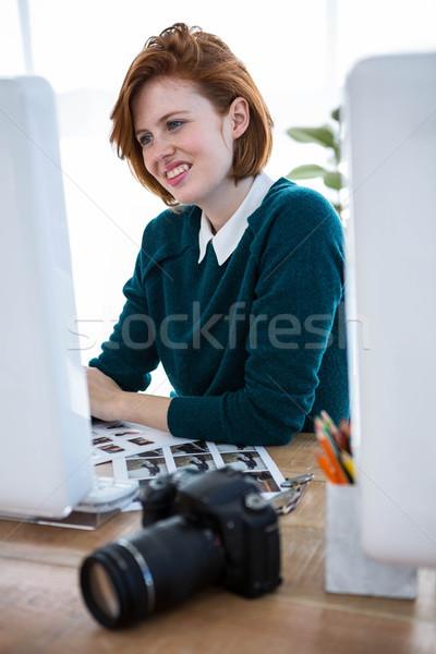 smiling hipster photographer on her computer Stock photo © wavebreak_media