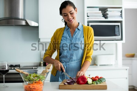 Stock photo: Portrait of beautiful woman learning food recipe from laptop
