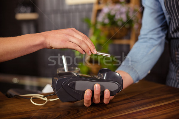 Female customer paying with smartphone Stock photo © wavebreak_media