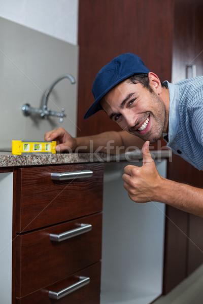 Smiling man showing thumbs up while using spirit level  Stock photo © wavebreak_media