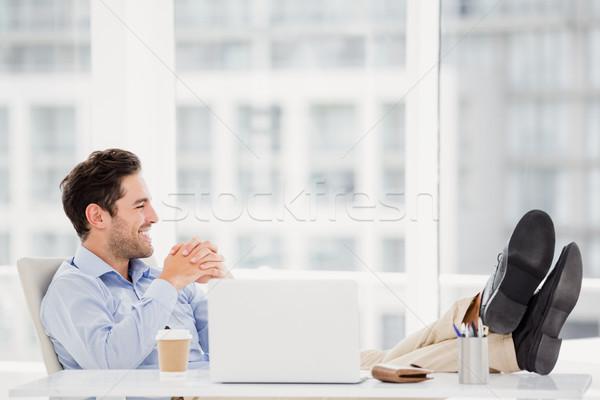 Thoughtful man sitting with feet on table Stock photo © wavebreak_media