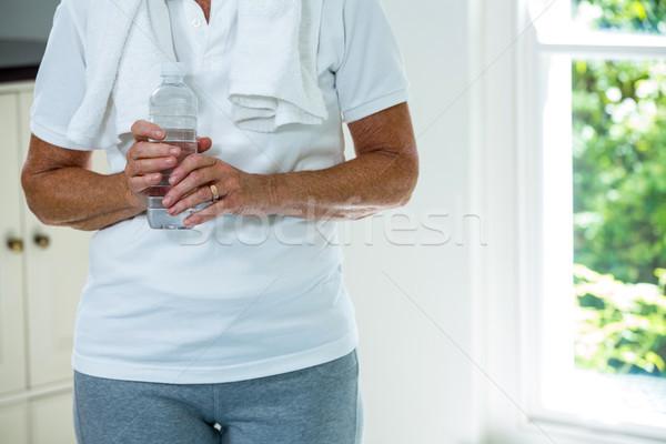 Senior vrouw permanente veldfles home Stockfoto © wavebreak_media