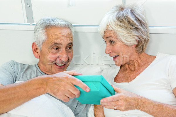 Senior man gifting to woman on bed Stock photo © wavebreak_media