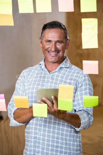 Man holding digital tablet and sticky notes on window Stock photo © wavebreak_media