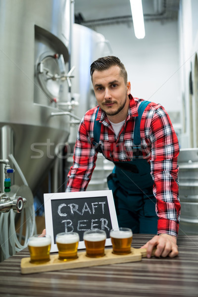 Portrait of brewer with four glasses of craft beer on table Stock photo © wavebreak_media