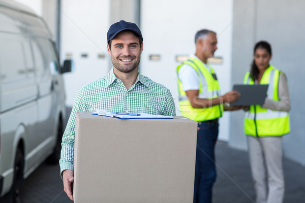 Focus of delivery man is holding a cardboard box and smiling to  Stock photo © wavebreak_media