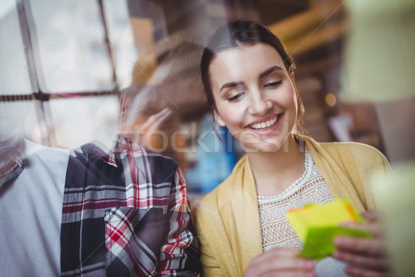 Businesswoman smiling while reading sticky notes  Stock photo © wavebreak_media