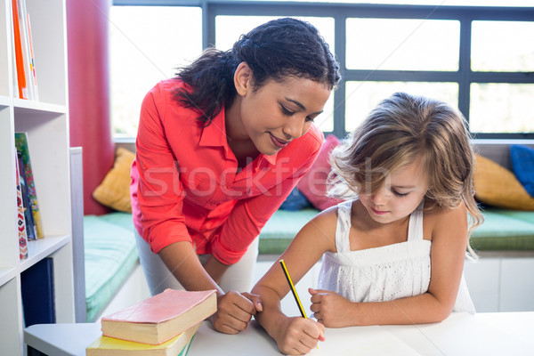 Teacher assisting girl writing on notebook in library Stock photo © wavebreak_media