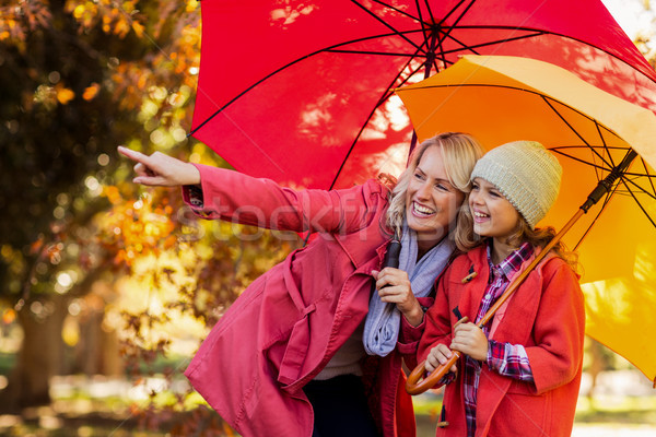 Feliz mulher indicação em pé filha guarda-chuva Foto stock © wavebreak_media