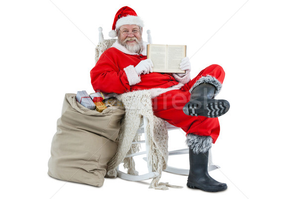 Santa claus showing bible with sack of christmas present beside him Stock photo © wavebreak_media