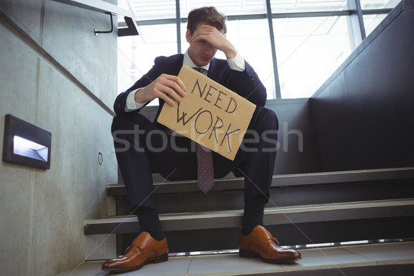 Depressed businessman sitting on stairs holding cardboard sheet with text need work Stock photo © wavebreak_media
