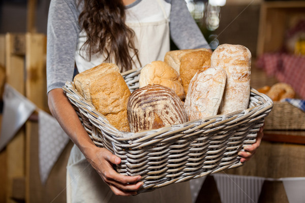 Female staff holding wicker basket of various breads at counter in bakery shop Stock photo © wavebreak_media