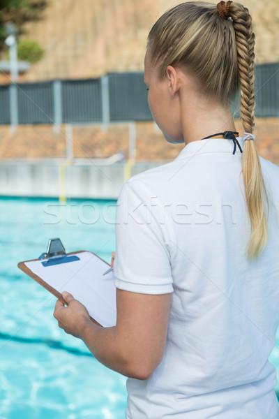 Female coach writing on clipboard at poolside Stock photo © wavebreak_media