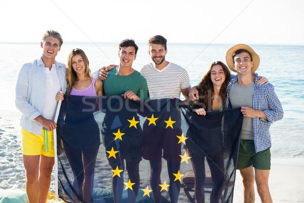 Friends holding European Union flag on shore at beach Stock photo © wavebreak_media