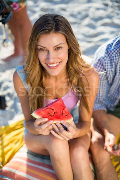 Happy woman having watermelon while sitting at beach Stock photo © wavebreak_media