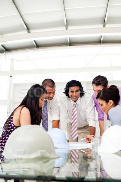 Multi-thnic engineer co-workers reviewing blueprints Stock photo © wavebreak_media
