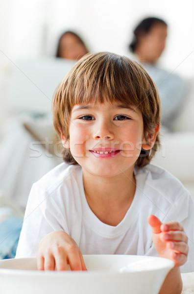 Smiling little boy eating chips lying on the floor  Stock photo © wavebreak_media