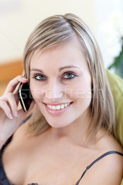 Radiant woman talking on phone sitting on a sofa Stock photo © wavebreak_media