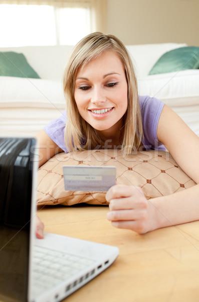 Smiling woman shopping on-line lying on the floor Stock photo © wavebreak_media