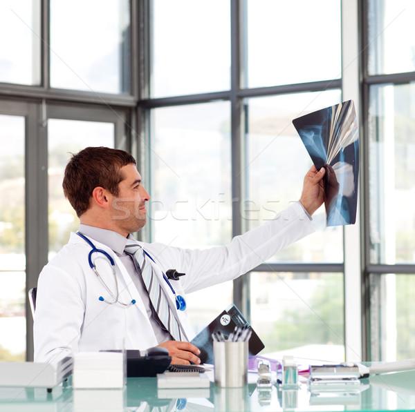 Male doctor examining a x-ray at his desk Stock photo © wavebreak_media