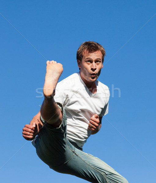 Smiling Man jumping in the air outdoor against a blue sky background Stock photo © wavebreak_media