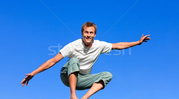 Jóképű férfi ugrik levegő szabadtér kék ég kezek Stock fotó © wavebreak_media