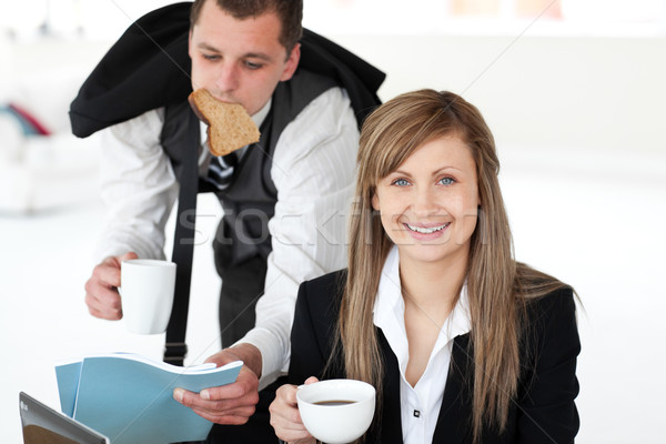 Glowing businesswoman holding a cup smiling at the camera her boyfriend taking papers and rush Stock photo © wavebreak_media