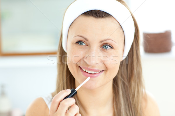 Attractive young woman using lipgloss in the bathroom at home Stock photo © wavebreak_media