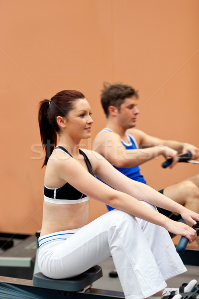 Athletic people using a rower in a fitness center Stock photo © wavebreak_media