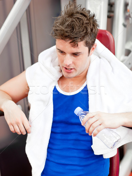Tired man with a towel and a bottle of water sitting on a bench press Stock photo © wavebreak_media