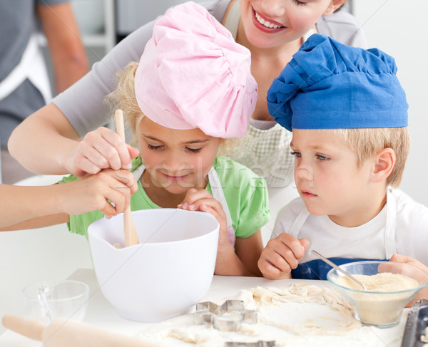 Two children and their mother stiring a preparation for cookies together in the kitchen Stock photo © wavebreak_media
